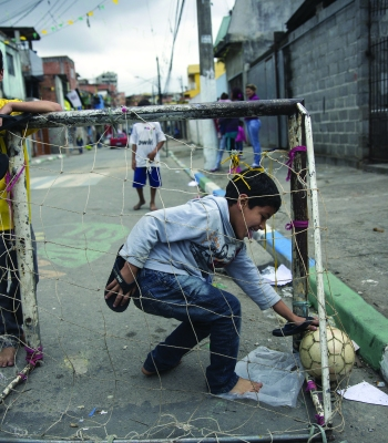 SAO PAULO, BRAZIL - JUNE 21:  Children play football in the street in the poor neighbourhood of Itaquera, adjacent to the 'Arena de Sao Paulo' stadium, on June 21, 2014 in Sao Paulo, Brazil. The Arena de Sao Paulo, which is reported to have cost in excess of 200 million GBP, hosted the opening match of the 2014 FIFA World Cup and has a capacity of over 61,000. The total cost borne by Brazil for staging the 2014 World Cup is estimated to be 6.5 billion GBP, which critics have argued would have better spent on the millions of Brazilians living in poverty.  (Photo by Oli Scarff/Getty Images)