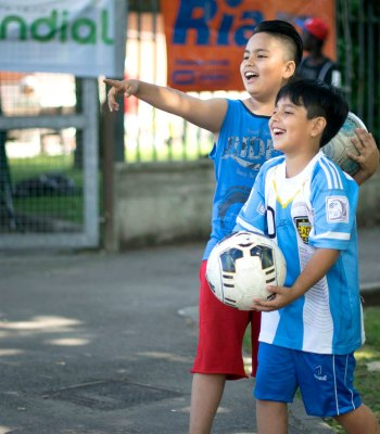 Two kids smiling and playing football.